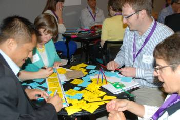 4 people at a table writing on post it notes at 2013 AAEEBL conference
